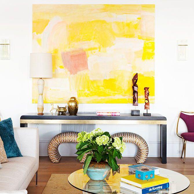 Una gran pintura abstracta blanca y amarilla está colgada sobre una mesa auxiliar con lámparas y otras piezas de arte.