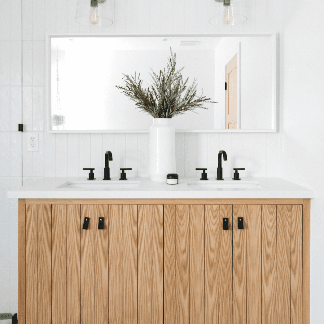 A bathroom lined with wood paneling that's been painted white