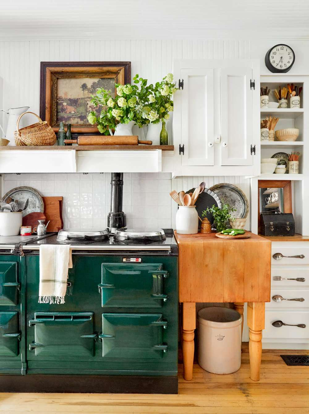 A small kitchen that's filled with kitchen utensils, wooden accents, and dark green appliances