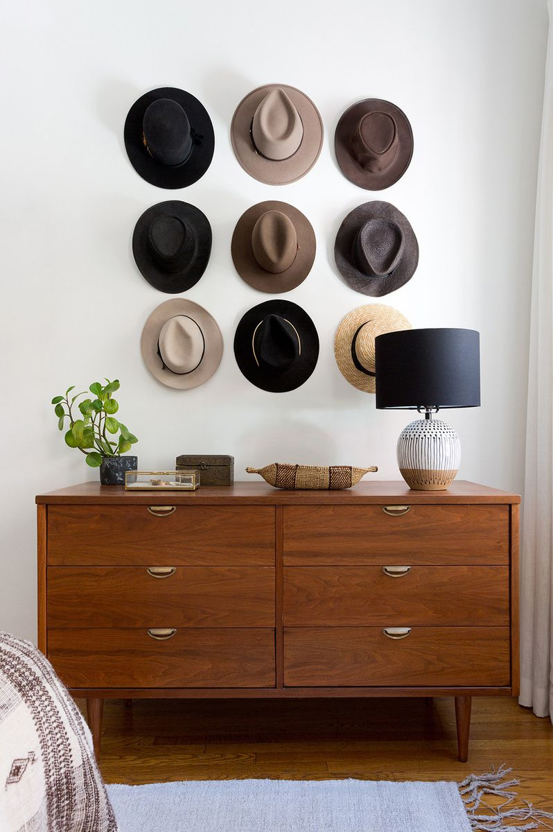 Mid-Century wood dresser with hanging collection of hats above