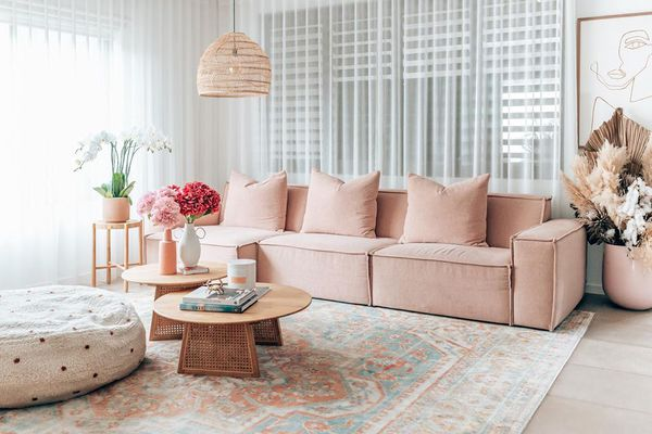 Pink sofa in front of blinds.