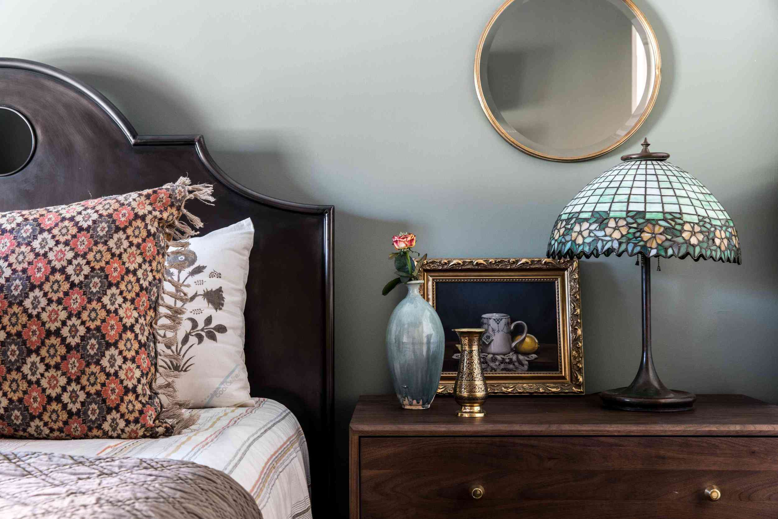 Traditional bedroom nightstand area with gray-green walls