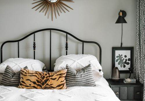 IKEA black bedframe with expensive looking comforter on top.