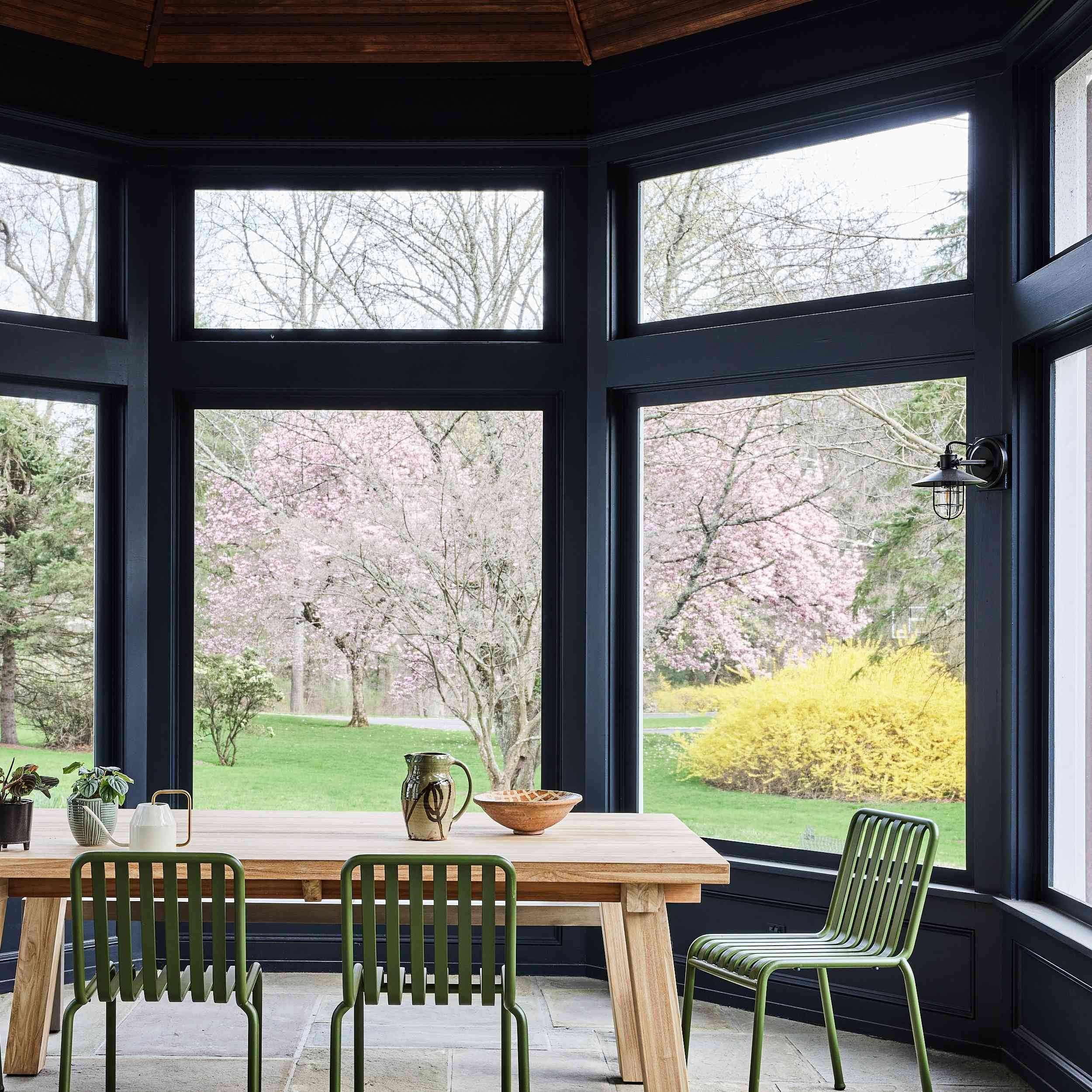 connecticut farmhouse home tour - solarium with green metal chairs and wood table
