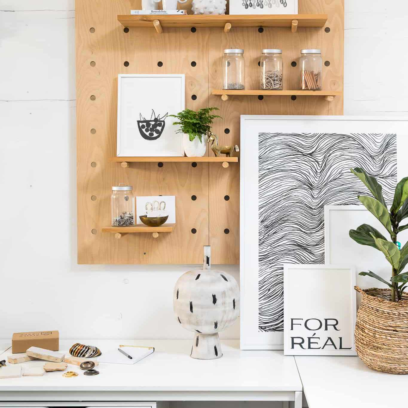 Desk decor with art and plants.