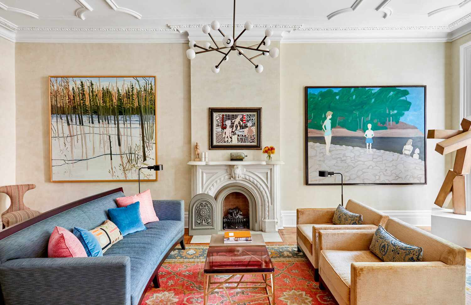 A living room with contemporary lighting, bold art, and a red printed rug