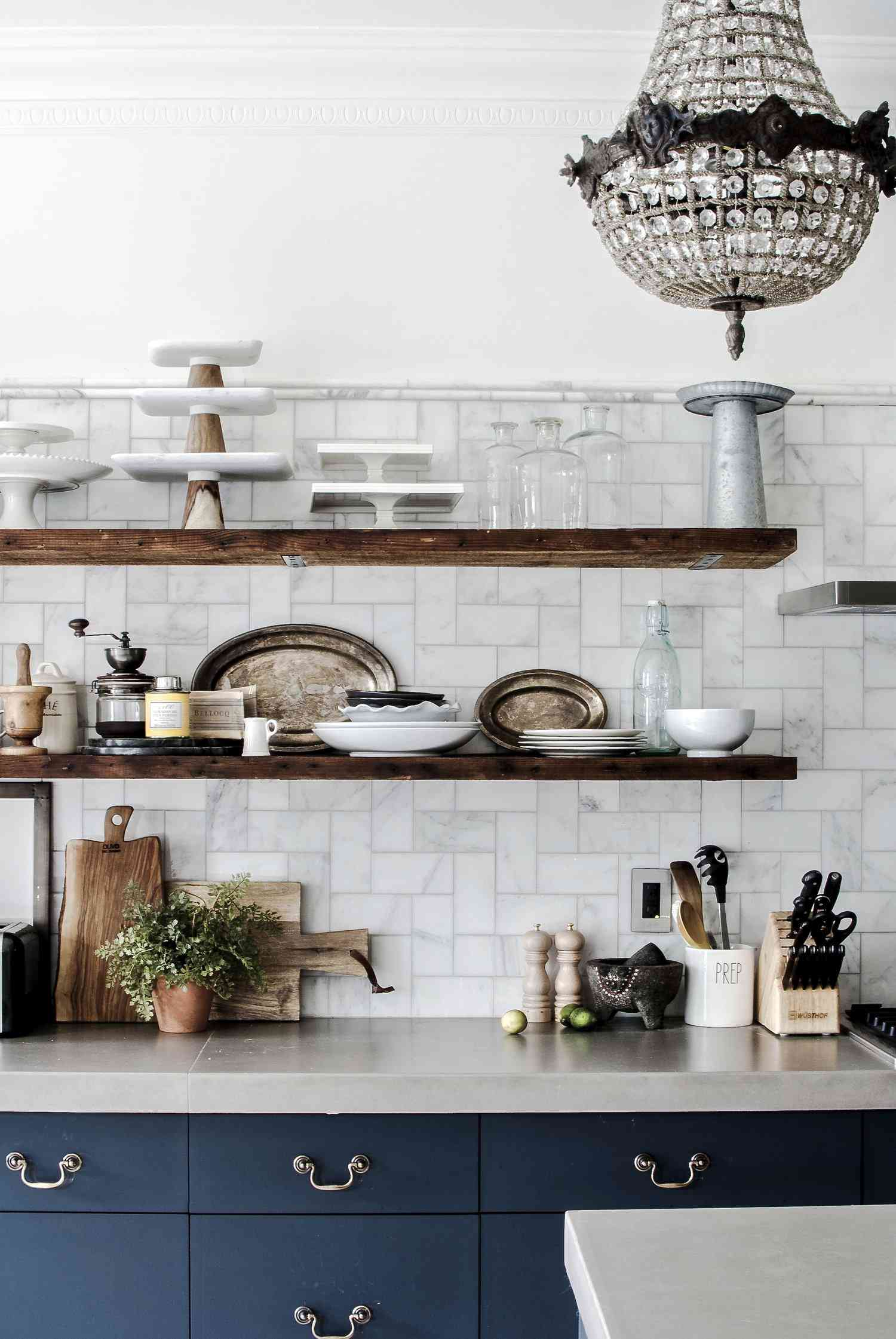 A set of kitchen shelves lined with ceramic cookware, rustic wooden items, and antique silver plates