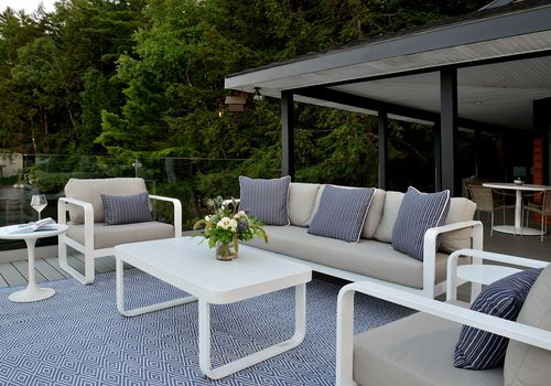 Outdoor patio with matching furniture set and rug.