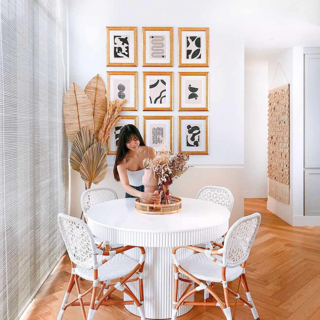 Casual dining room with textured white table, bistro chairs, and a gallery wall of abstract collages