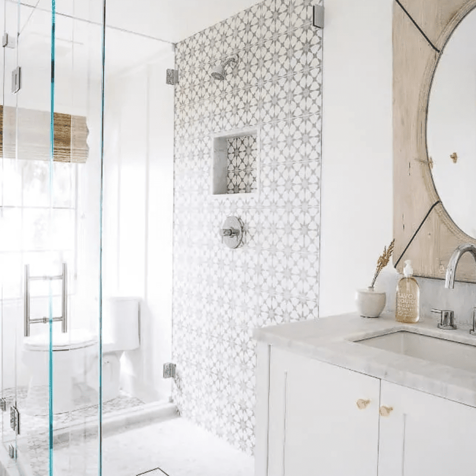 A bathroom with a boldly tiled shower wall and matching floors