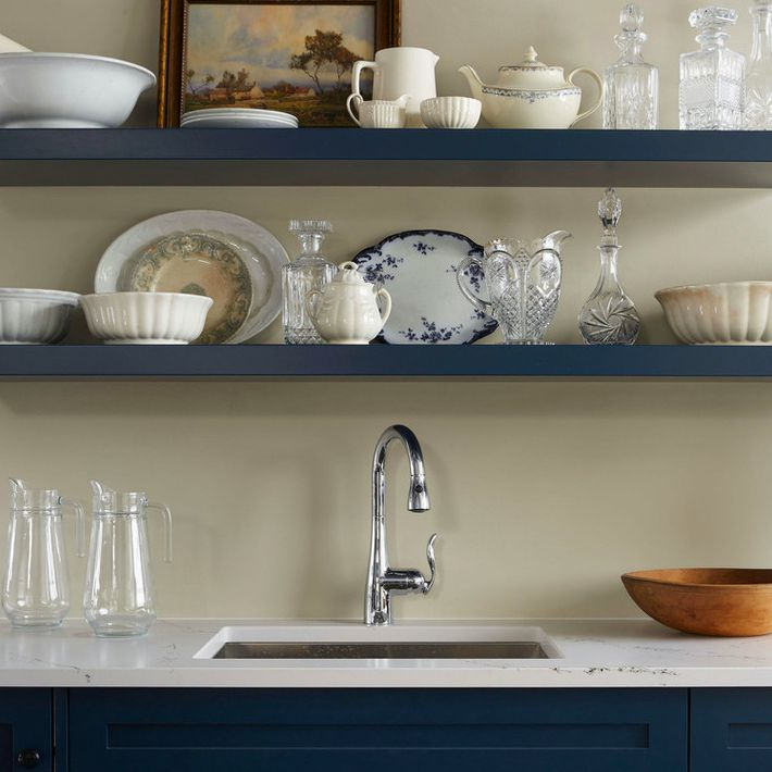 Dark blue open shelving displaying antique dishes, crystal decanters, and a painting