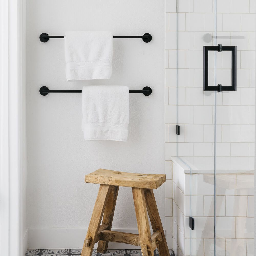 Shower area with graphic tile, wood stool, and matte black hardware