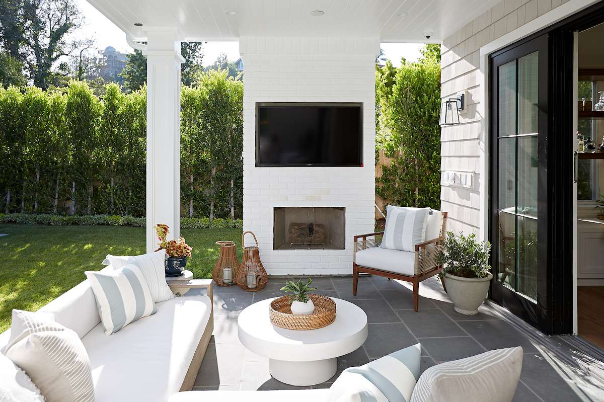 A patio with an outdoor fireplace and a TV mounted just above it