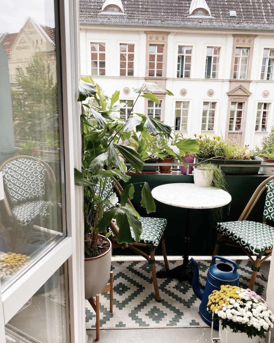 balcony with patterned green chairs, green rug, lots of plants