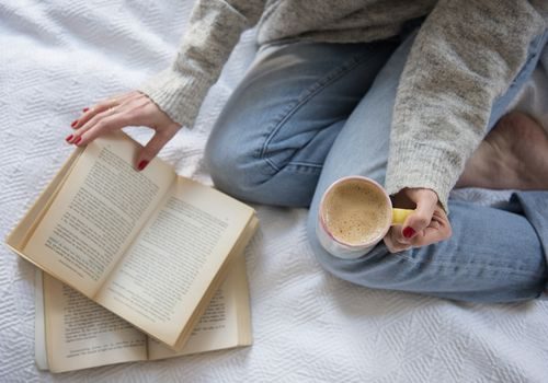 person reading books with mug of coffee