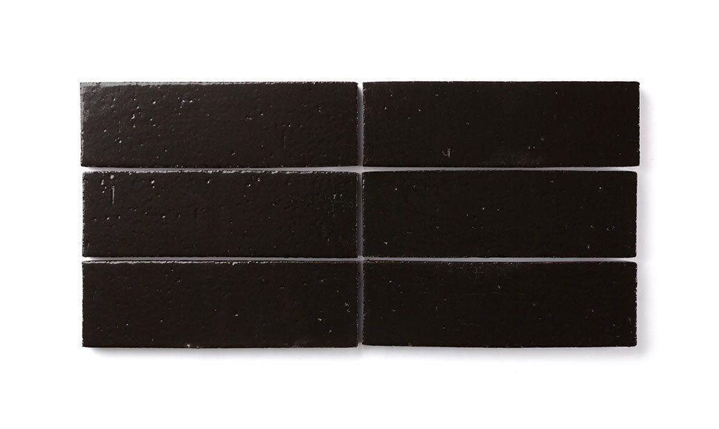 Piezas de azulejos de ladrillo en rodajas en negro.
