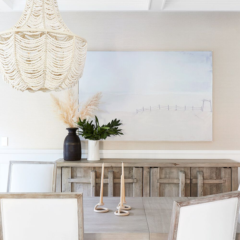 An all-white dining room decorated with a pastel blue painting