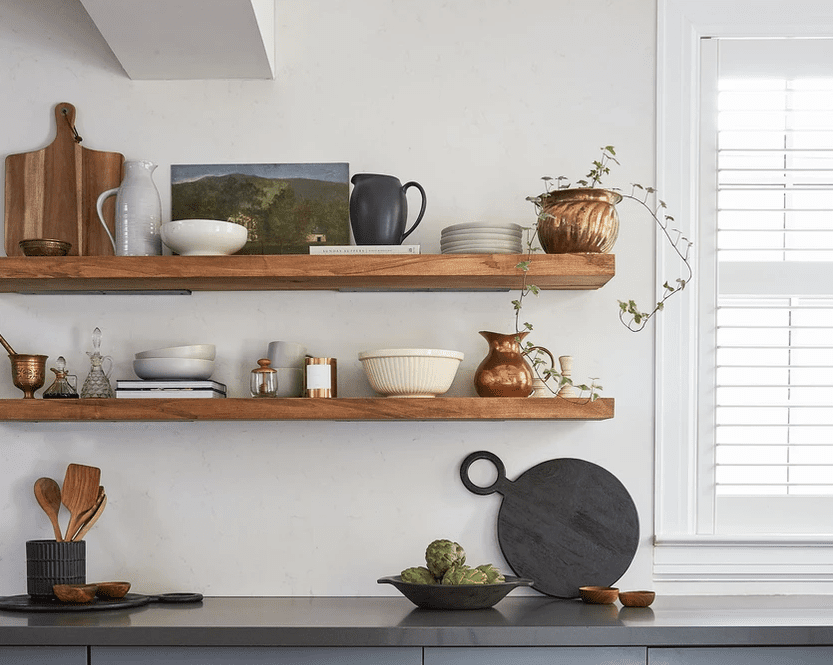 Shelf in kitchen filled with vintage cookware.
