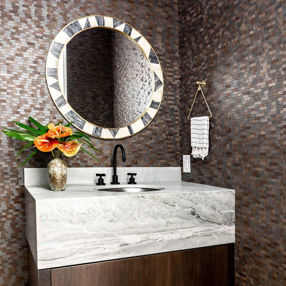 Marble bathroom sink, wraparound tiled walls, round mirror with patterned border