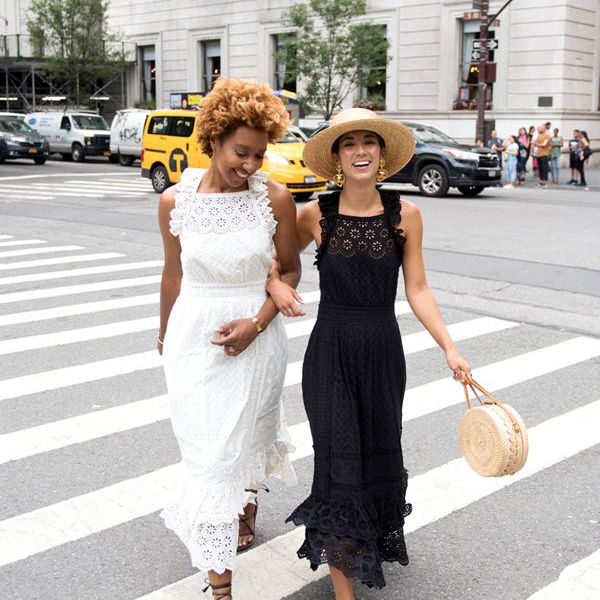 two women walking arm in arm in a cross walk