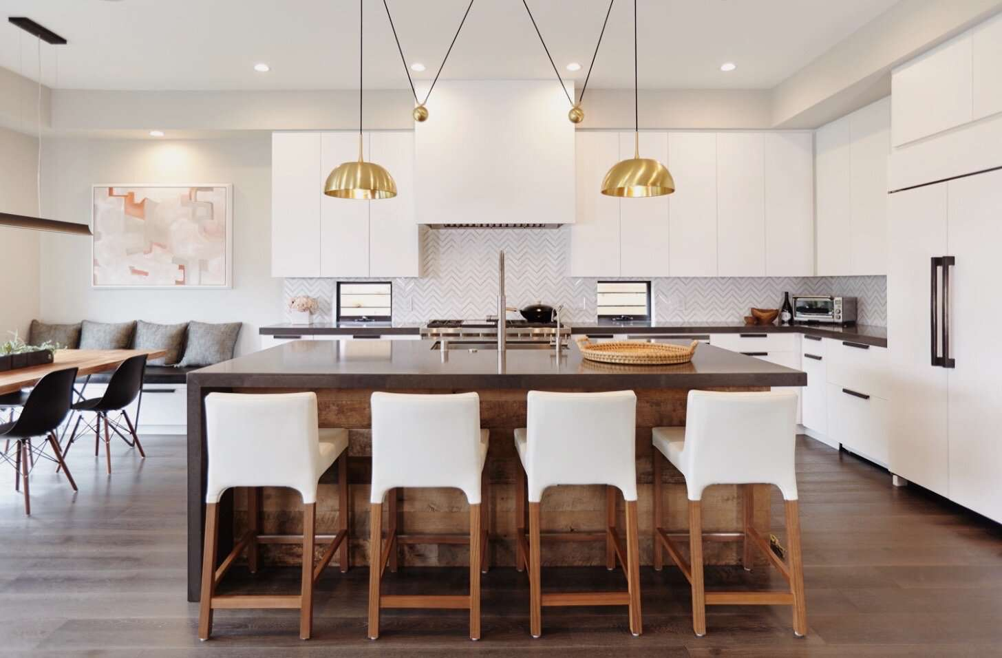 All white kitchen with brown kitchen island and gold domed lighting
