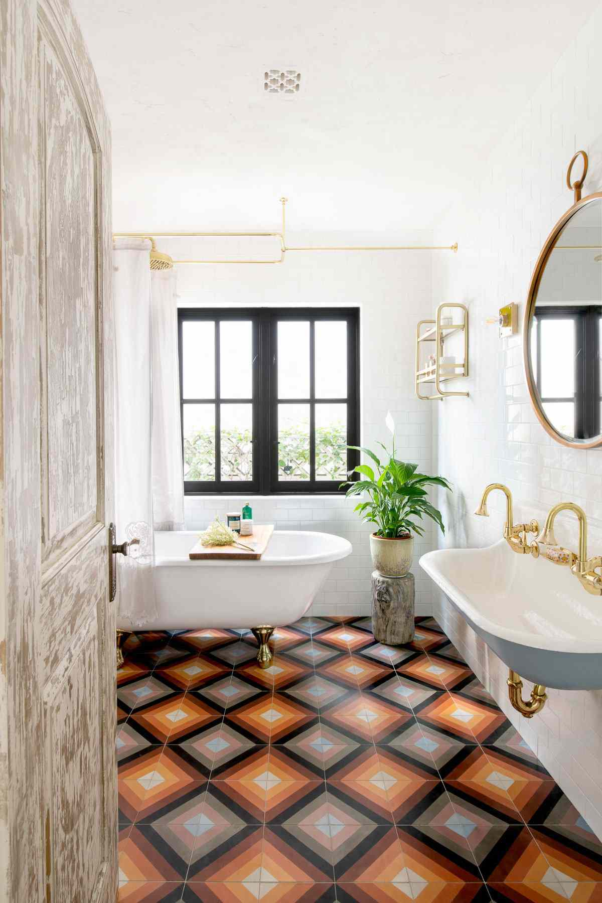 A small primary bathroom with a boldly tiled floor, a clawfoot tub, and a wall-mount sink