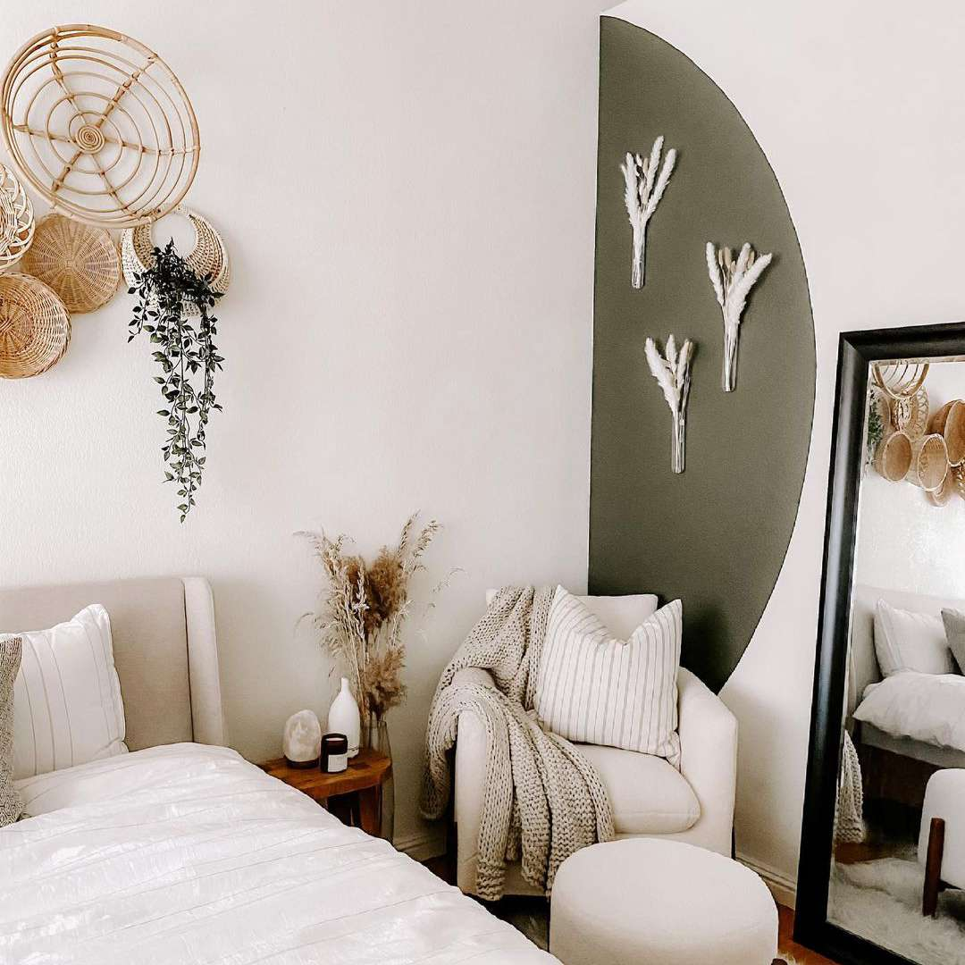 Bedroom with neutral furniture and olive green painted arch.