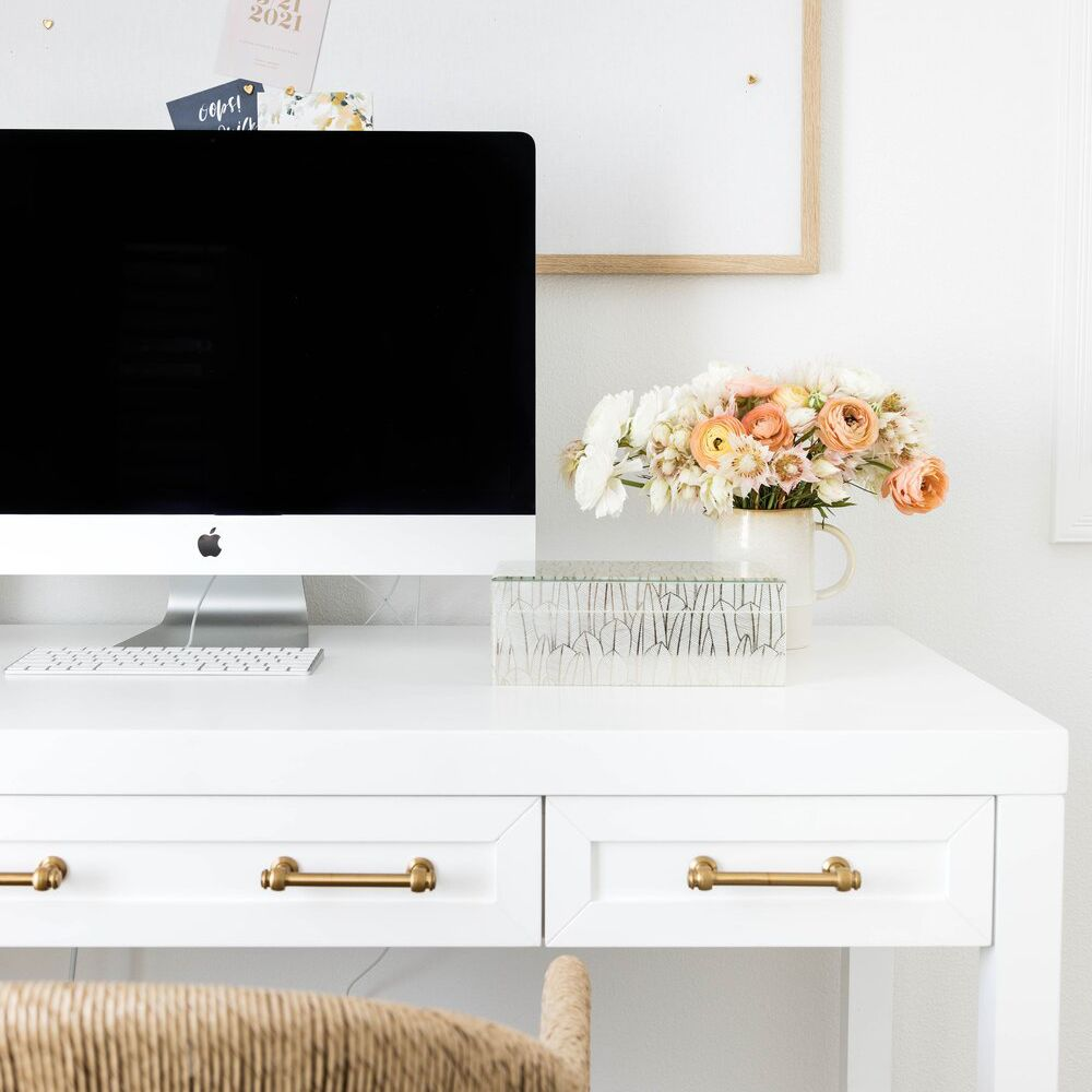 White desk with Mac and pinboard with cards