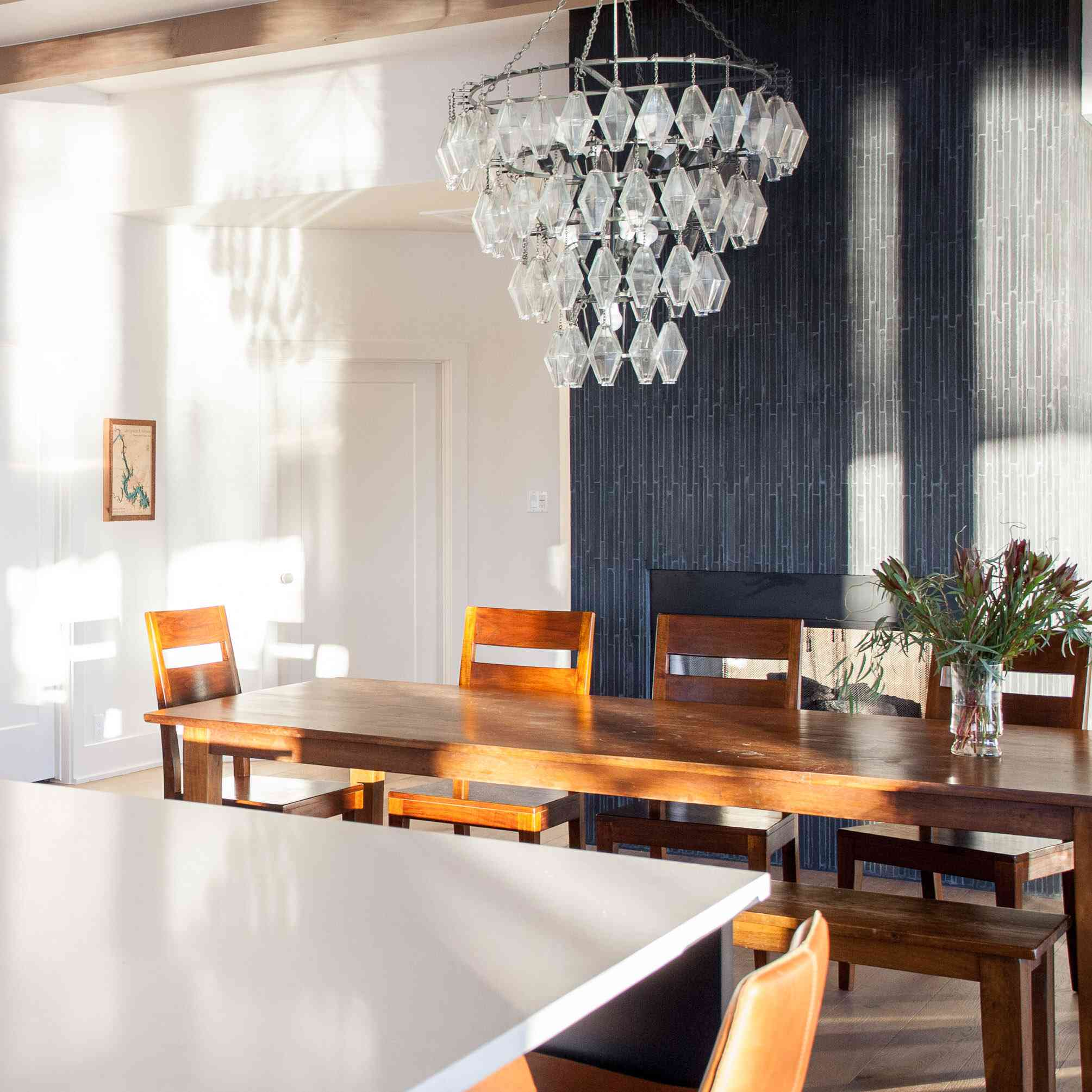 A dining room flanked by a fireplace-lined wall that's been covered with textured navy wallpaper
