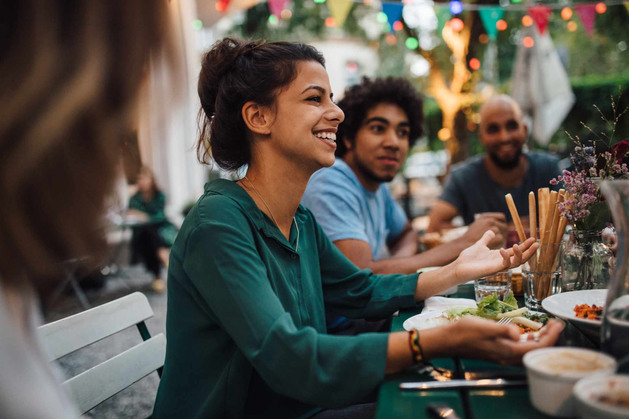 Young woman smiling, surrounded by friends at outdoor dining table