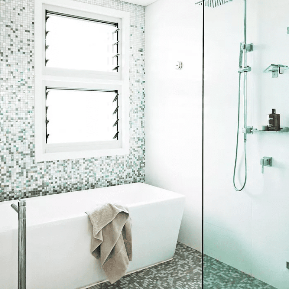 Gradient-tiled bathroom with square white tub and modern fixtures