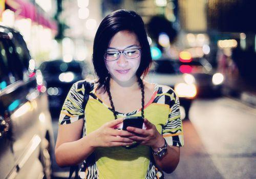 Mujer indonesia al teléfono por la noche: Foto de archivo Comp Insertar Compartir Agregar al tablero Título: Una mujer indonesia joven y moderna escribe en su teléfono inteligente en una calle de la ciudad por la noche Mujer indonesia al teléfono por la noche