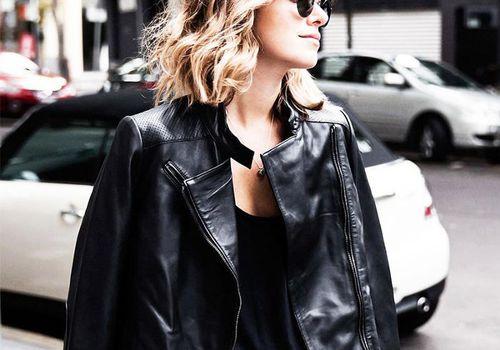 woman dressed in black standing on city street