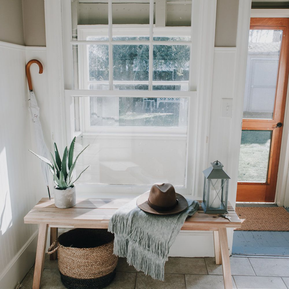 Foyer features wood bench, woven basket, potted plant