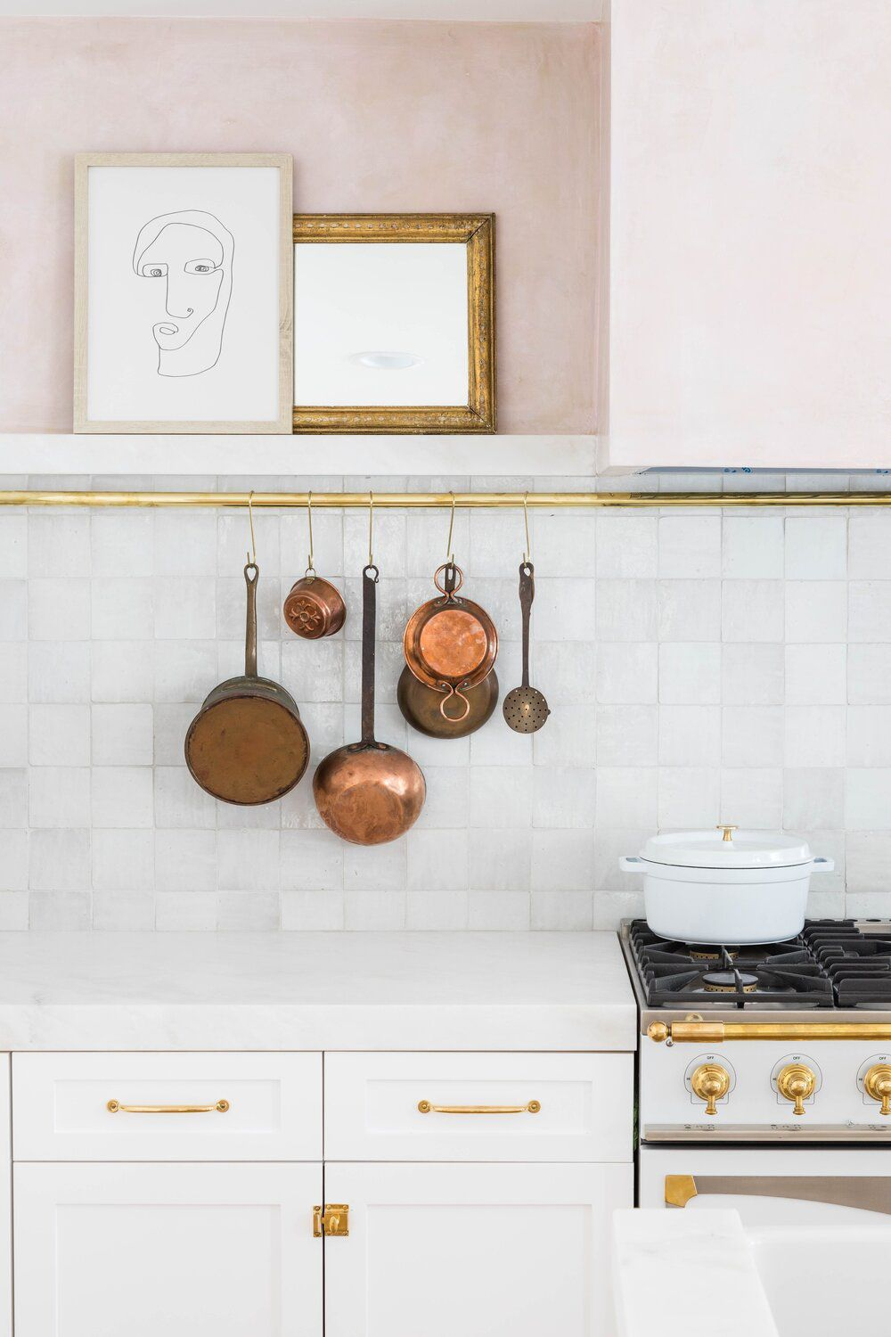 A white and pink kitchen with a metal rod holding several rustic copper pots