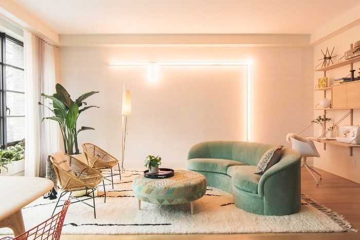 Salón en tonos melocotón con sofá verde curvado