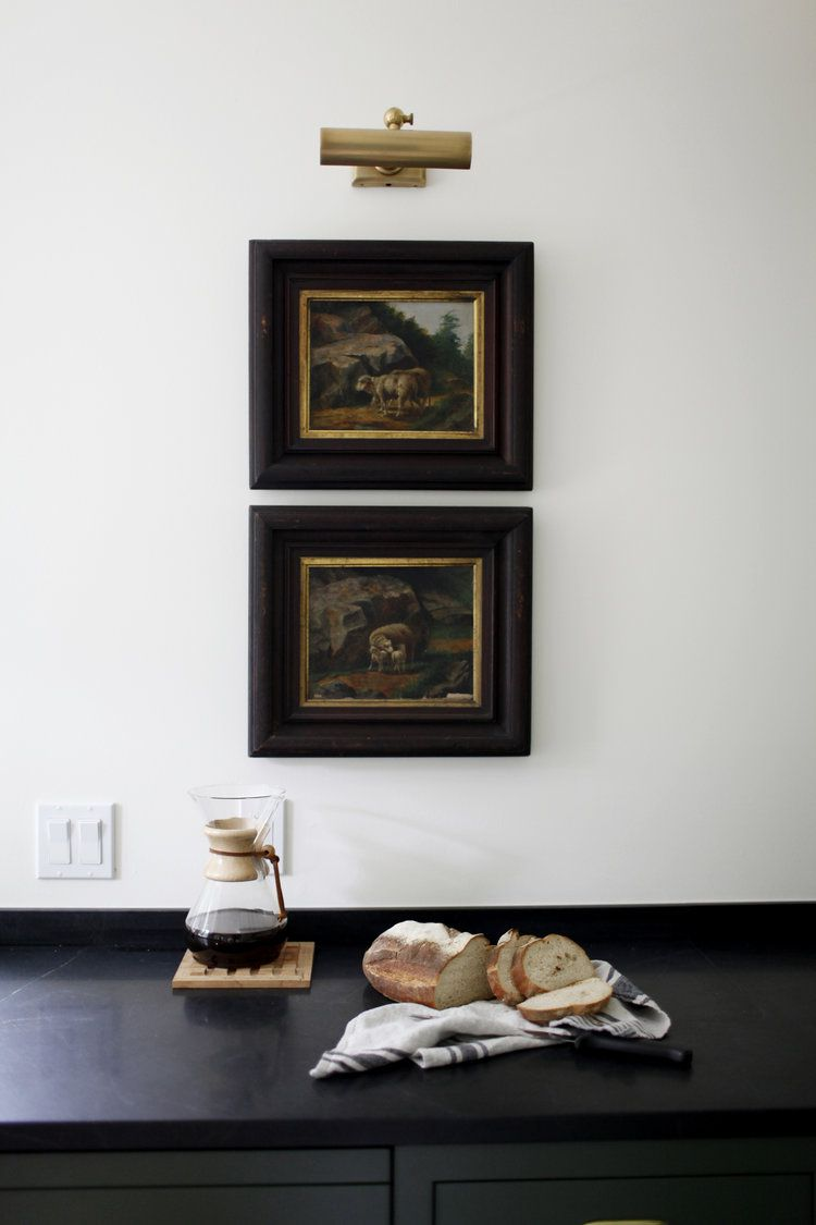 A kitchen wall lined with rustic art