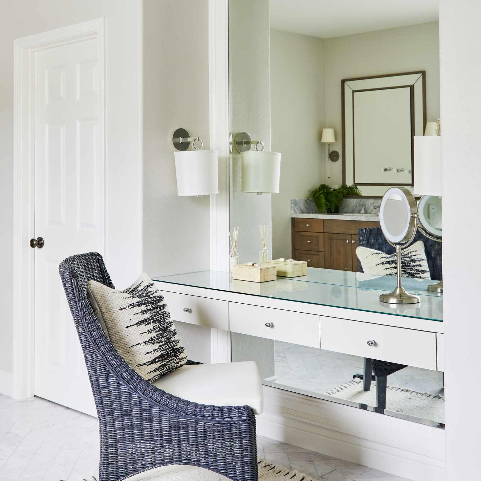 Elegant vanity space with large wicker chair.