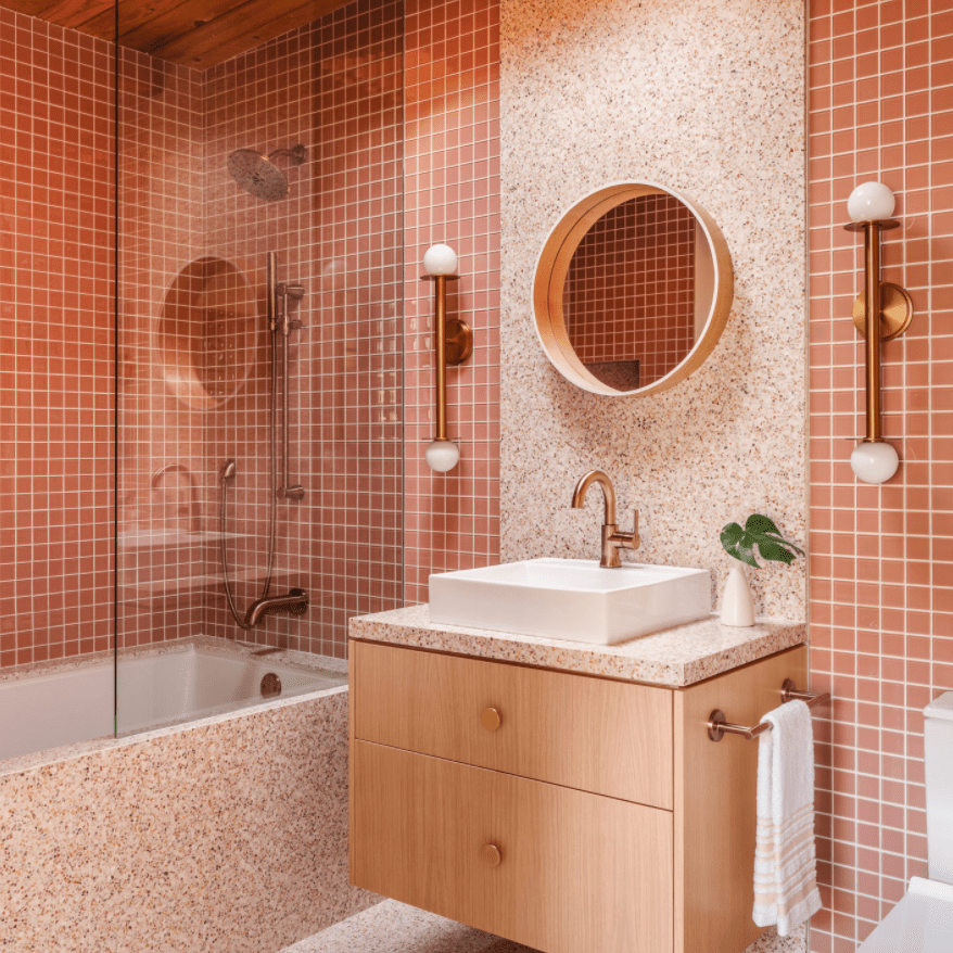 A monochromatic bathroom lined with pink tiles and pink terrazzo slabs
