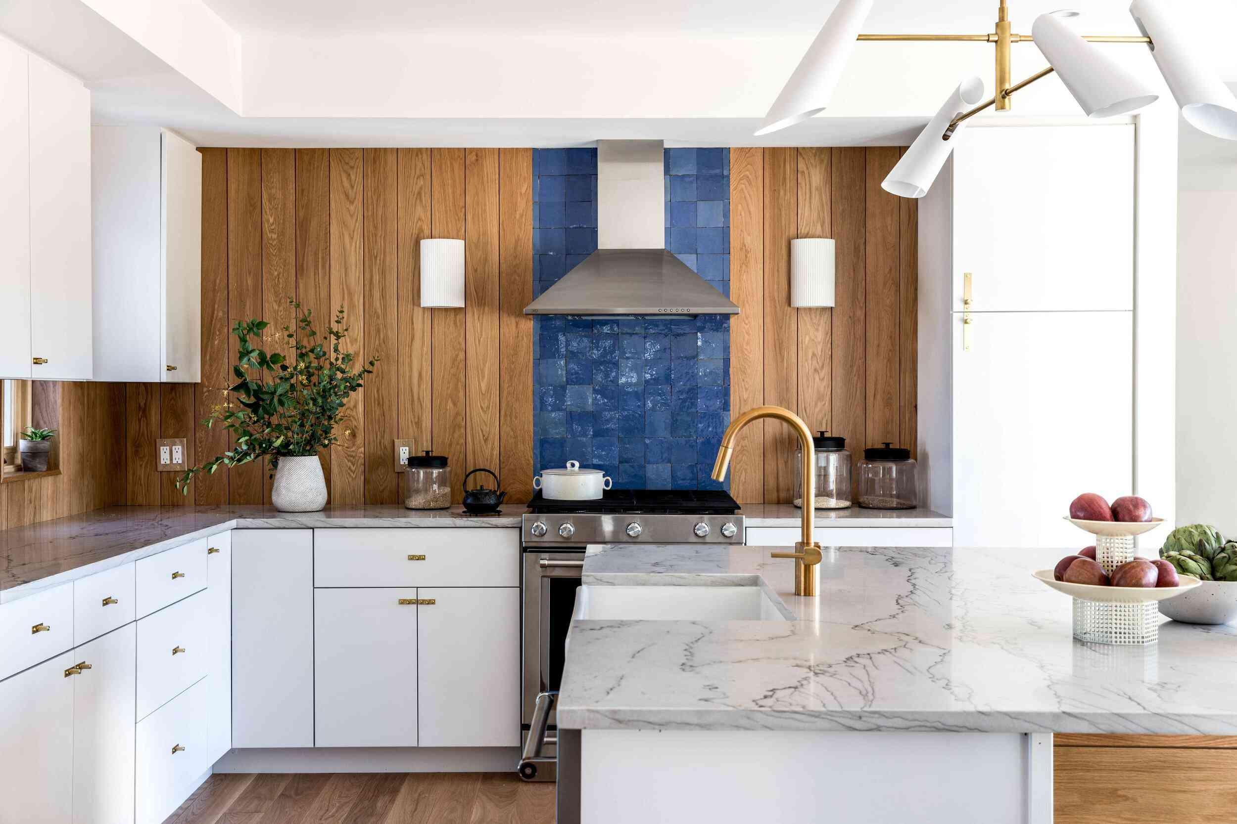 A wood-paneled kitchen with a bold blue backsplash