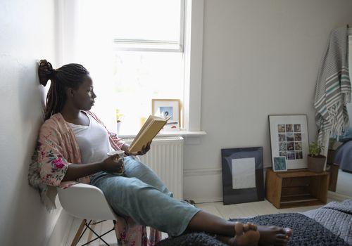 Mujer joven relajante, tomando café y leyendo un libro en el dormitorio