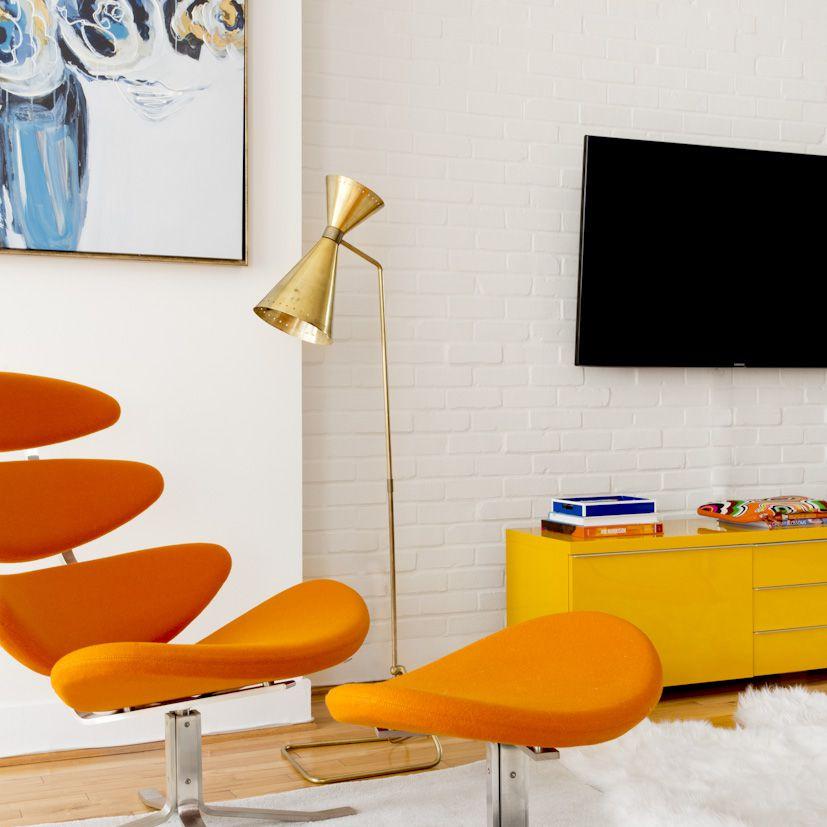 white brick wall in modern colorful apartment, orange retro chair