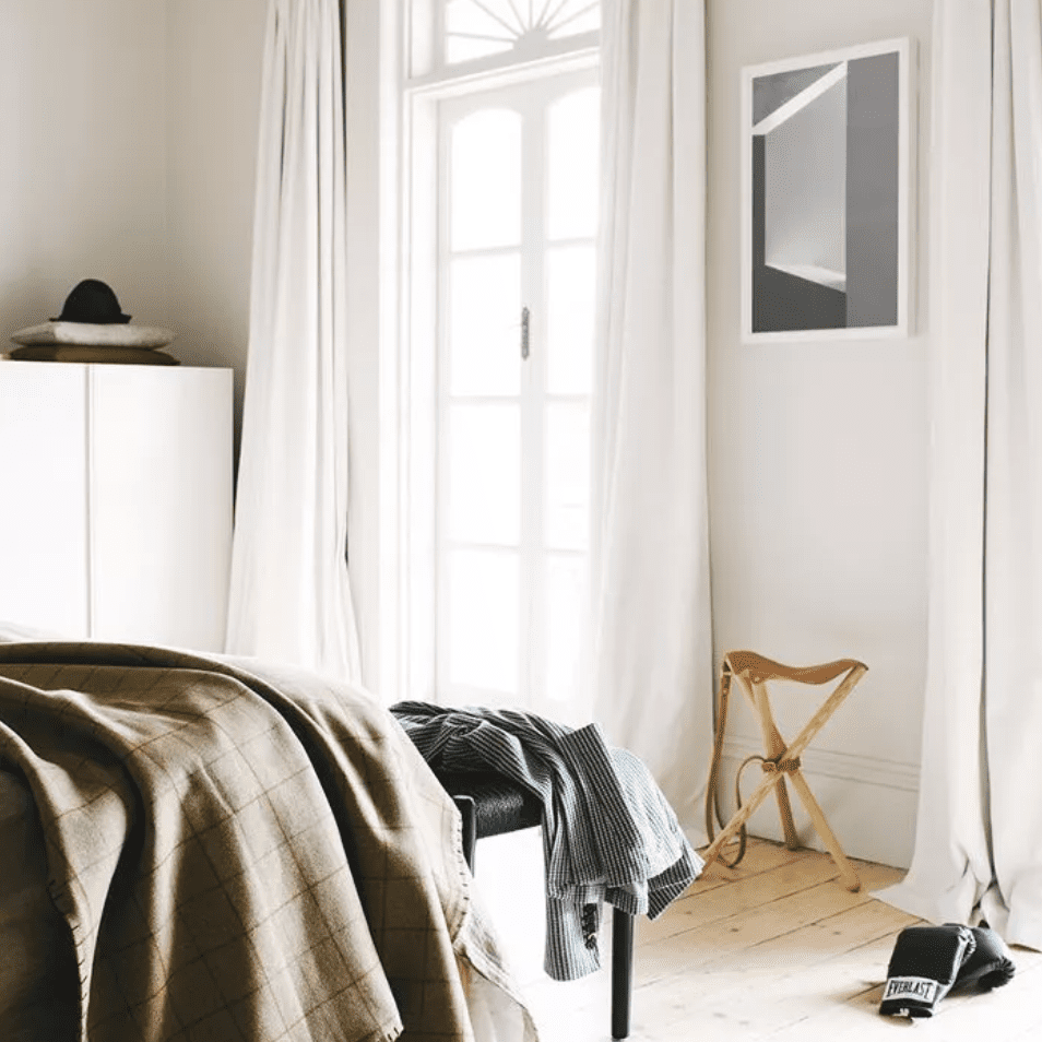 Floor length white curtains frame a window in a bedroom