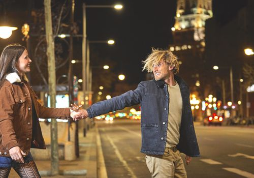 man and woman holding hands at night