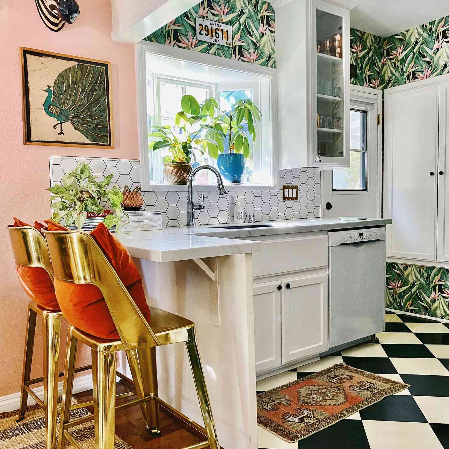 Small kitchen with graphic wallpaper, metallic stools, and pink walls.