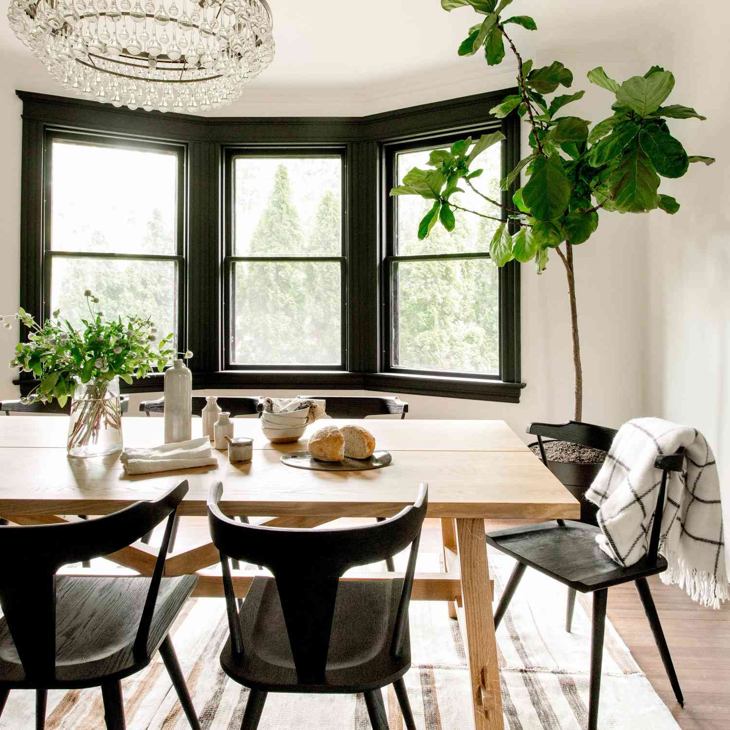 A dining room with rustic furniture and a glam chandelier