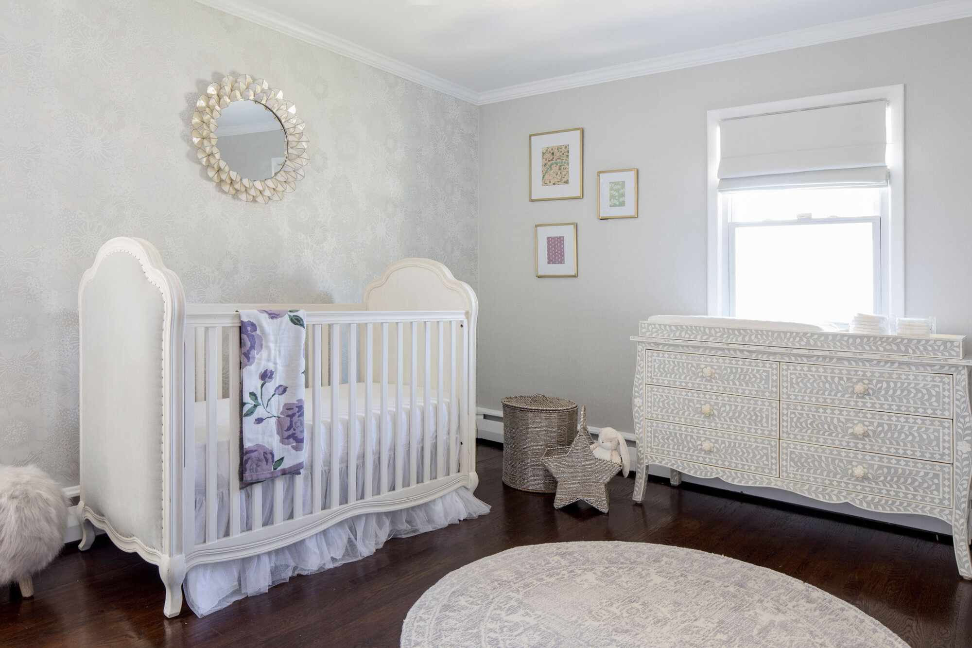 white nursery with light purple accents, vintage dresser
