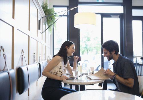 Pareja en cita en el restaurante sonriendo y hablando