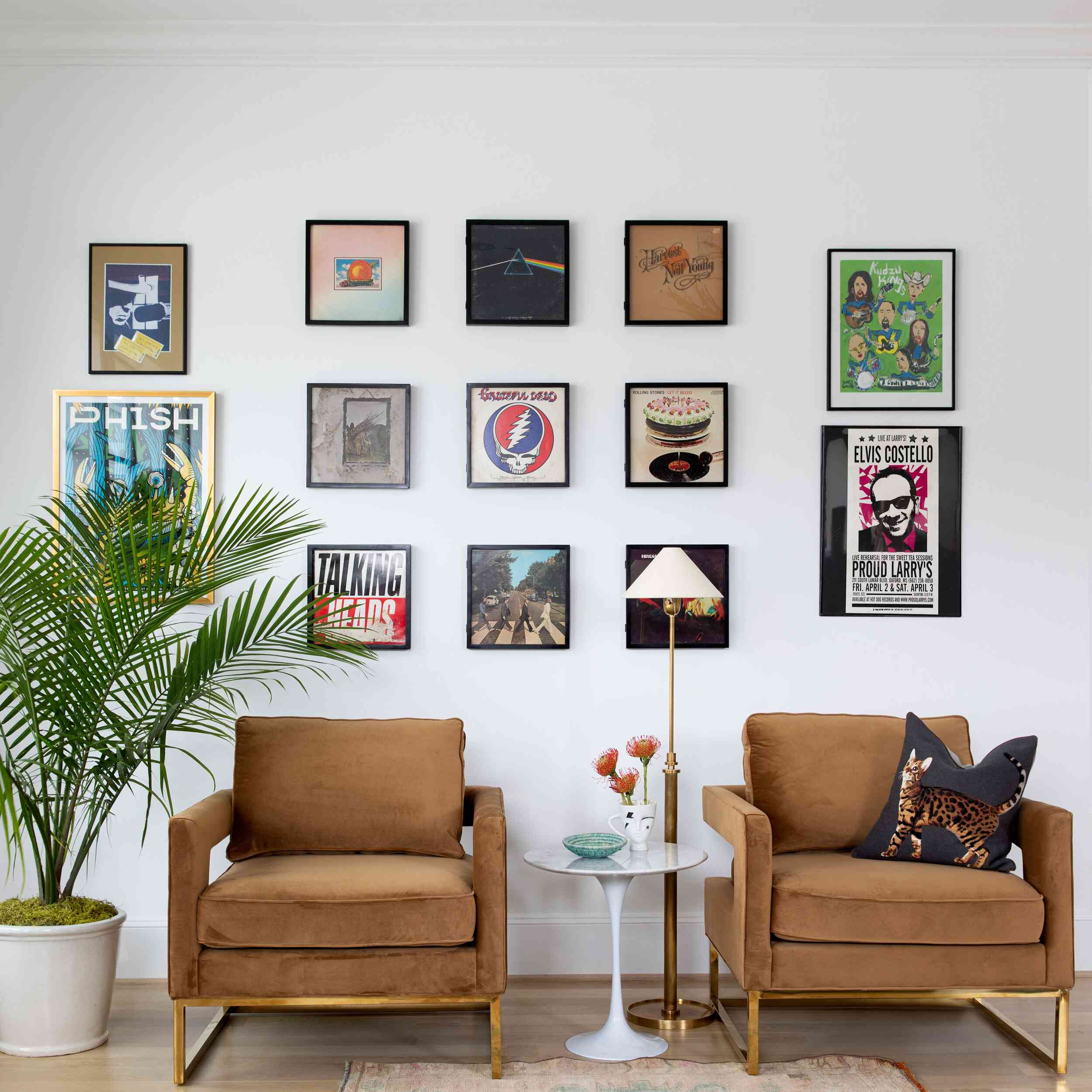 A living room with two lounge chairs and lots of framed graphic art