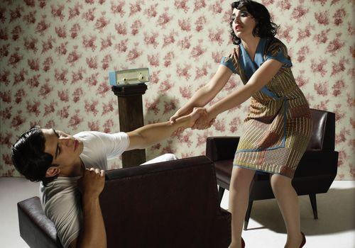 Una pareja discutiendo en una sala de estar.